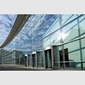Blick auf die geschwungene Glasfassade des Neuen Museums Nürnberg. Foto: Neues Museum, Anna Seibel.